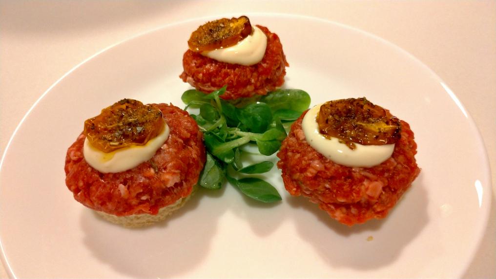 Amuse bouche: crostino di pane bianco, tartare alle erbe aromatiche, salsa greca, pomodorino giallo confit